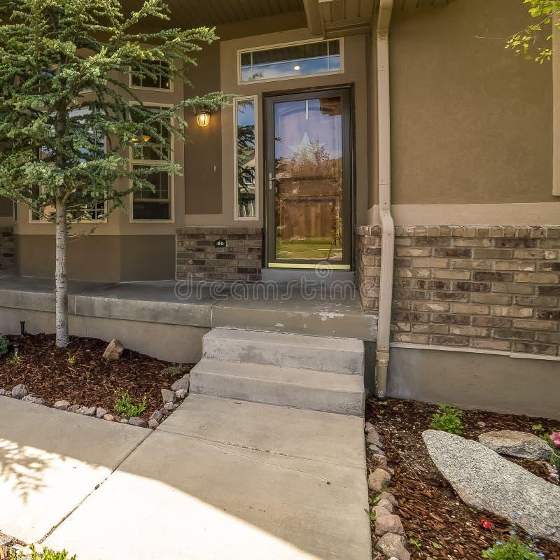 Façade à la maison de cadre carré avec la vue du porche et de l'entrée principale de porte de garage de yard un jour ensoleillé photo stock