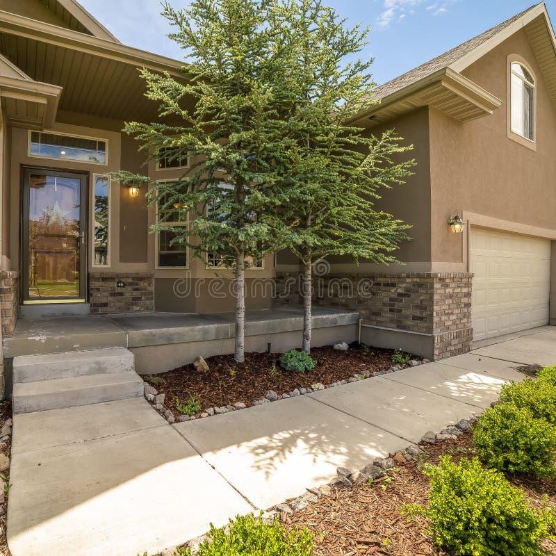 Façade à la maison de place avec la vue du porche et de l'entrée principale de porte de garage de yard un jour ensoleillé image libre de droits