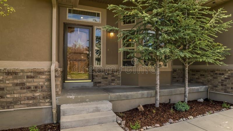 Façade à la maison de vue avec la vue du porche et de l'entrée principale de porte de garage de yard un jour ensoleillé images libres de droits