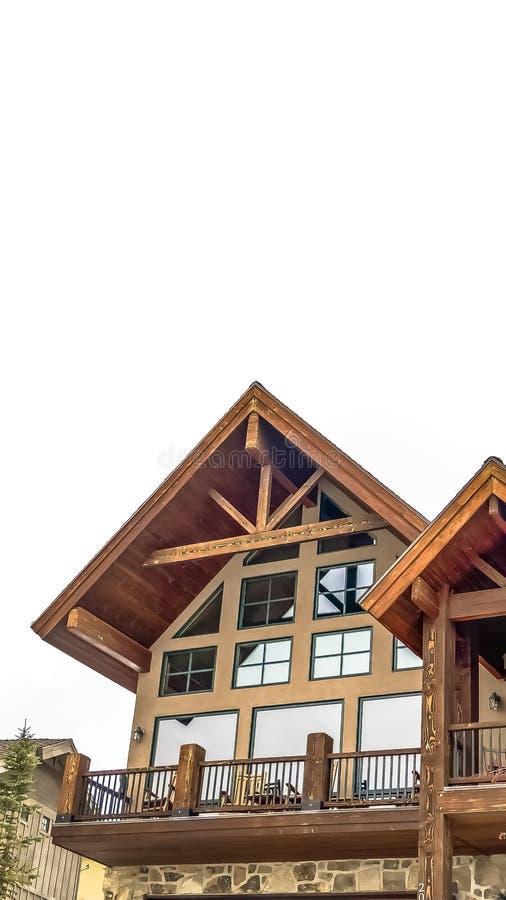 Façade à la maison verticale avec le balcon en bois d'accents et fenêtres brillantes contre le ciel nuageux image stock