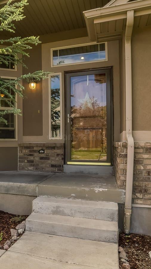 Façade à la maison verticale avec la vue du porche et de l'entrée principale de porte de garage de yard un jour ensoleillé photo stock