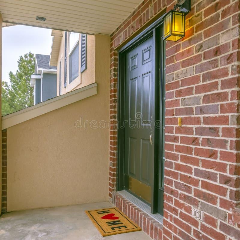 Façade carrée claire d'une maison avec un petit porche et un mur de briques rouge classique image libre de droits