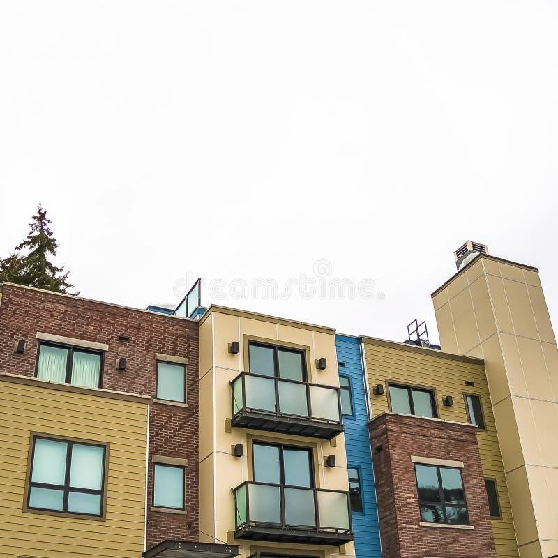 Façade carrée de bâtiment résidentiel de cadre avec le toit plat et balcons avec les balustrades en verre photographie stock