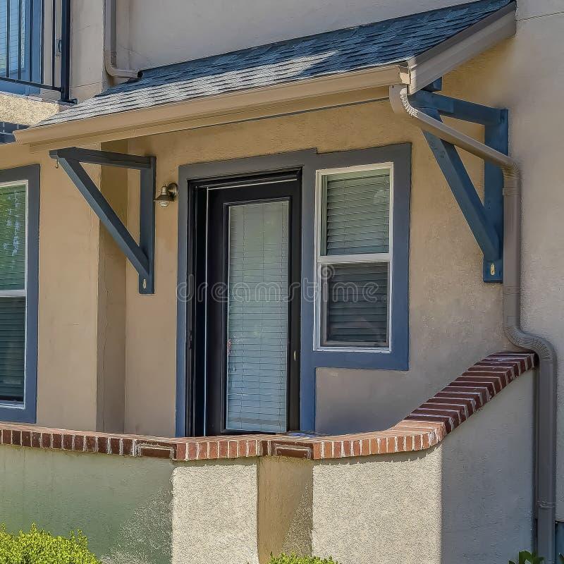 Façade carrée de maison avec la voie qui mène à l'entrée principale paned de porche et en verre photos stock