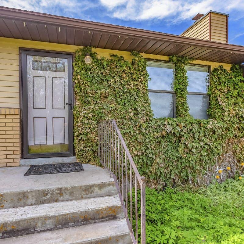 Façade carrée de vue d'une maison avec la vue de la porte et de l'entrée principale de garage contre le ciel bleu photos libres de droits