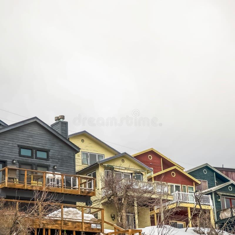 Façade carrée des maisons de montagne avec les balcons de dégrossissage horizontaux et les escaliers extérieurs photos stock