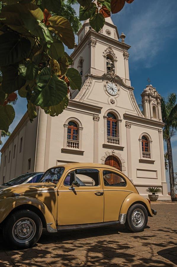 Façade d'église avec le jardin garé de voiture et d'arbre dans un jour ensoleillé chez São Manuel photos stock