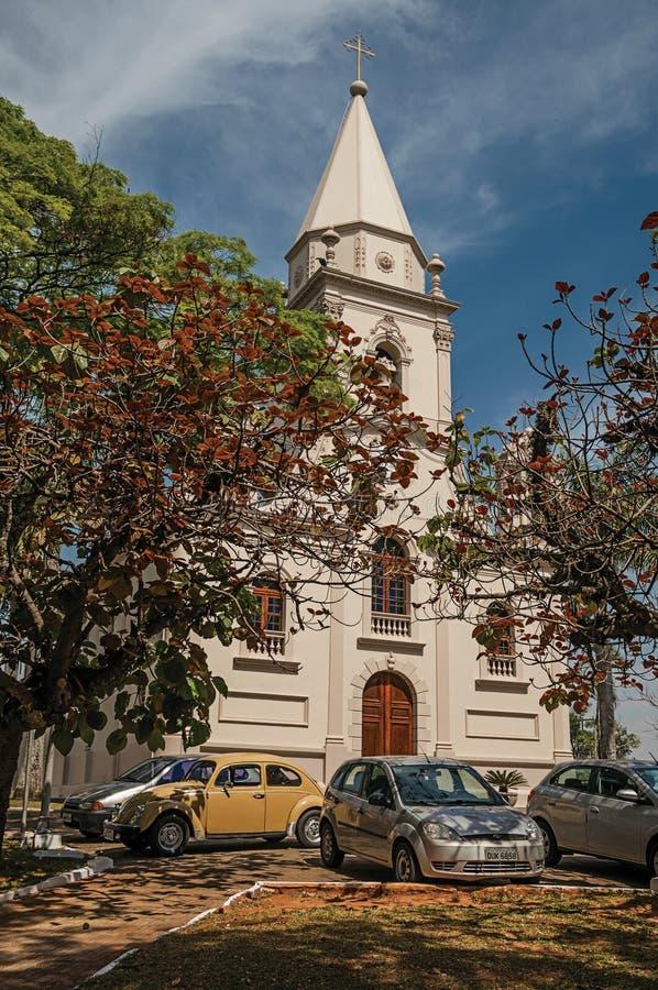 Façade d'église avec les voitures garées et jardin à feuilles persistantes dans un jour ensoleillé chez São Manuel photos stock