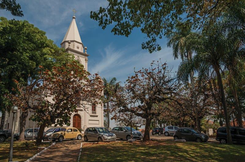 Façade d'église avec les voitures garées et jardin à feuilles persistantes dans un jour ensoleillé chez São Manuel images libres de droits