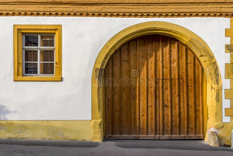 Façade d'une maison à colombage reconstituée en partie plâtrée avec la fenêtre et l'allée avec la voûte ronde et la porte en bois images stock
