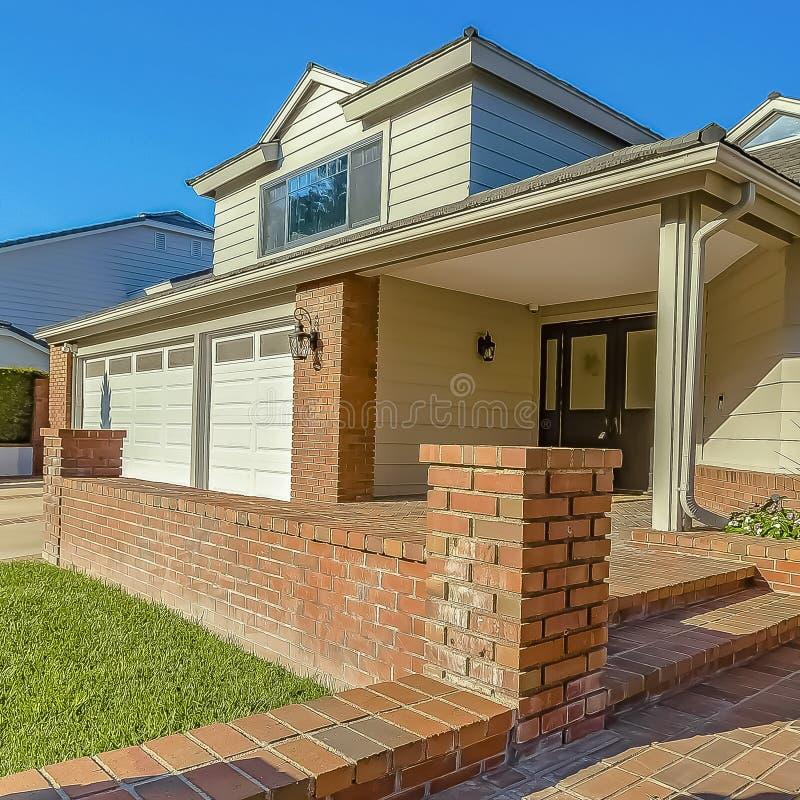 Façade d'une maison avec un patio et des escaliers extérieurs pavés avec les briques rouges rustiques photo stock