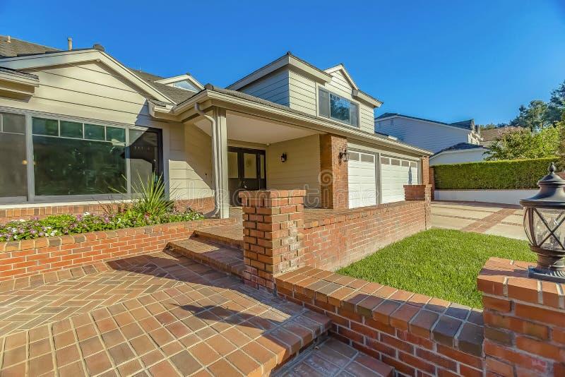 Façade d'une maison avec un patio et des escaliers extérieurs pavés avec les briques rouges rustiques photographie stock libre de droits