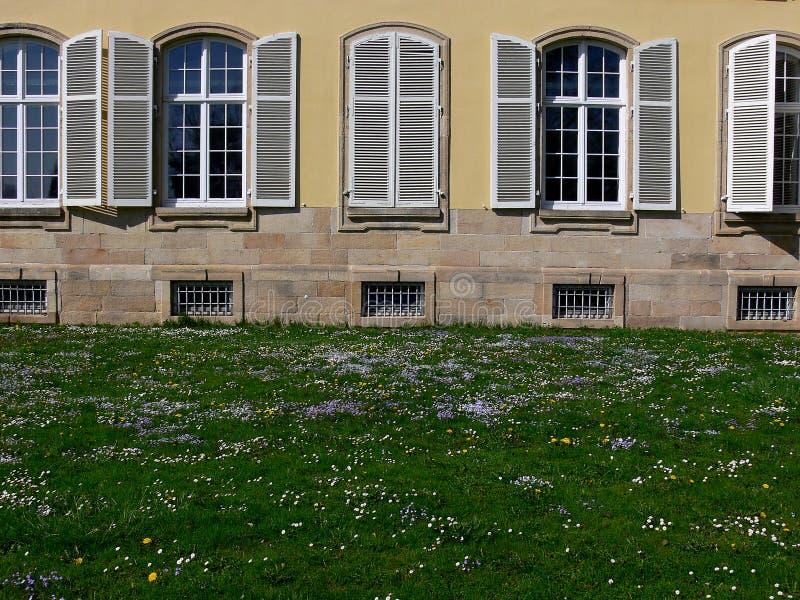 Façade de château avec les fenêtres et les volets semi-circulaires derrière le pré de fleur photos libres de droits