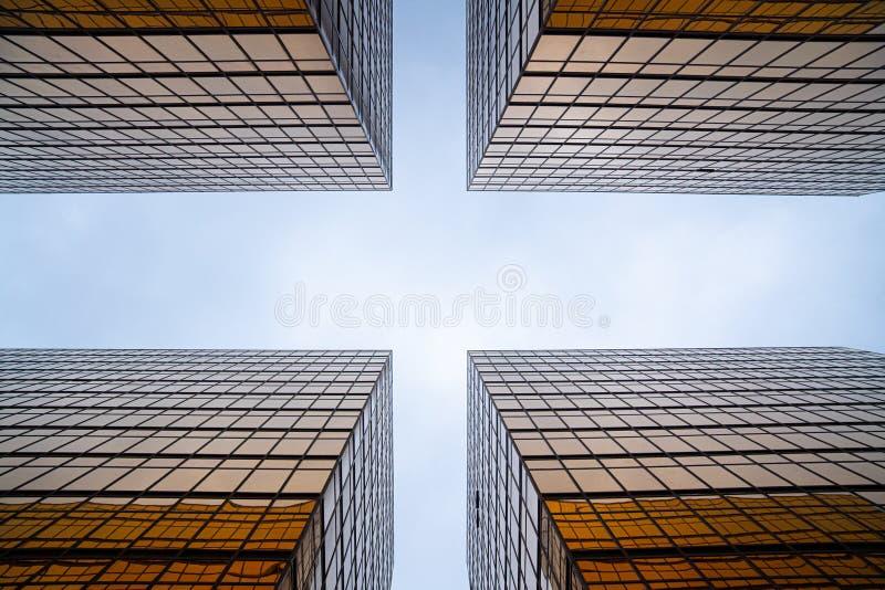Façade de construction en verre d'or dans la vue d'oeil de ver dans la vue croisée pour voir le ciel clair/architecture abstraite images stock