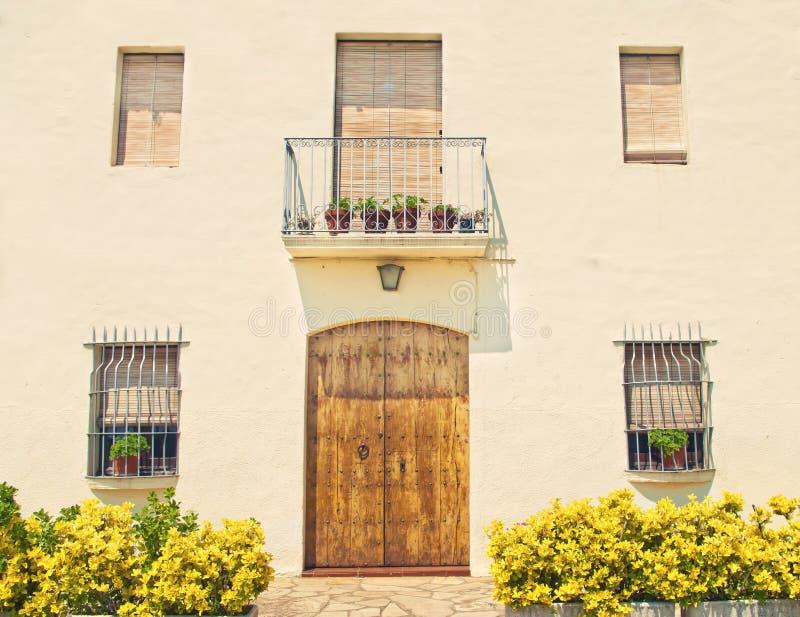 Façade européenne de maison avec la porte, les fenêtres et les usines en bois image libre de droits