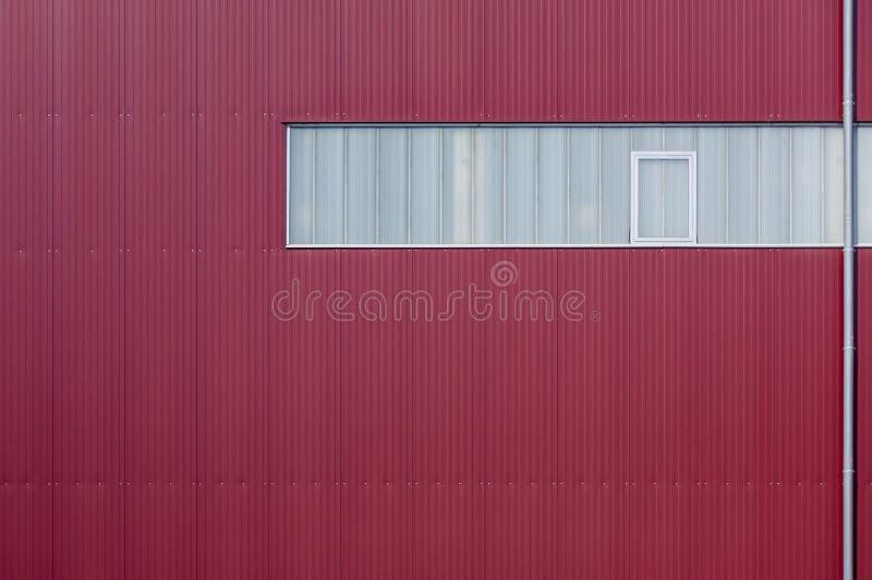 Façade moderne d'usine plaquée avec les éléments rouges et une bande de lumière images stock