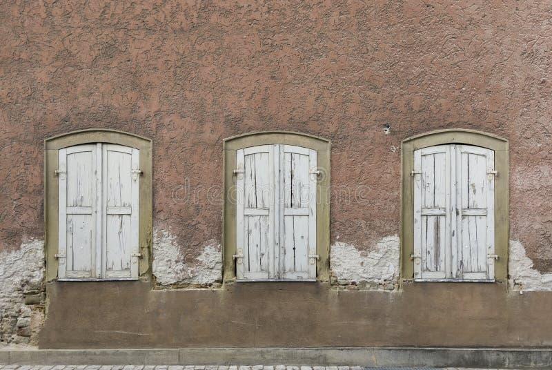 Façade symétrique de maison abandonnée et délabrée avec 3 fenêtres avec des volets photos libres de droits