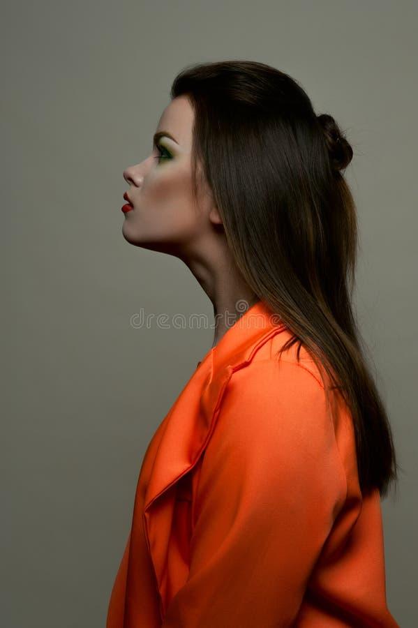 Façonnez à beauté la brune femelle avec les lèvres rouges et la veste orange image stock