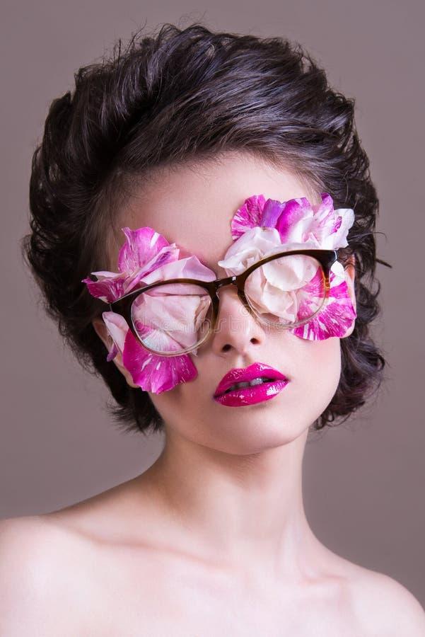 Façonnez à beauté la fille modèle portant les lunettes élégantes pleines des pétales de rose renivellement créateur de coiffure image libre de droits
