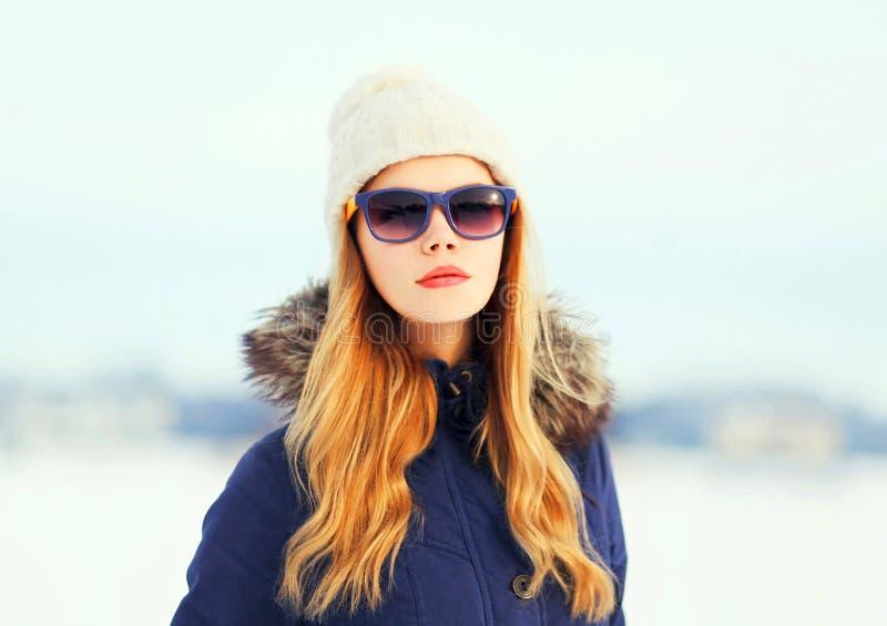 Façonnez à femme assez blonde de portrait d'hiver les lunettes de soleil de port d'un chapeau de veste photographie stock