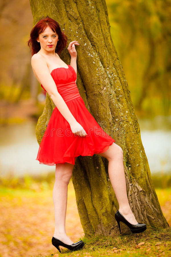 Façonnez à femme la marche de détente de robe rouge en parc images stock