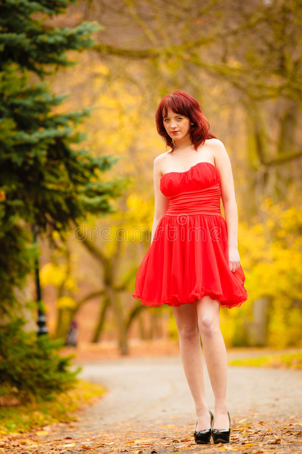 Façonnez à femme la marche de détente de robe rouge en parc photos stock