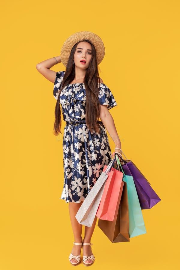 Façonnez à port de jeune femme de portrait les paniers, chapeau de paille, robe posant au-dessus du fond jaune coloré photographie stock libre de droits