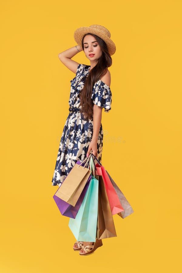 Façonnez à port de jeune femme de portrait les paniers, chapeau de paille, robe posant au-dessus du fond jaune coloré image stock