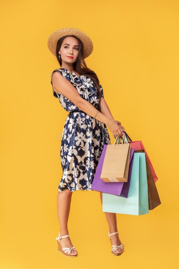 Façonnez à port de jeune femme de portrait les paniers, chapeau de paille, robe posant au-dessus du fond jaune coloré photographie stock