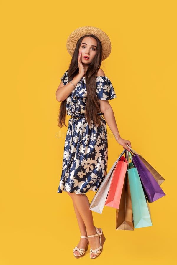 Façonnez à port de jeune femme de portrait les paniers, chapeau de paille, robe posant au-dessus du fond jaune coloré photos libres de droits