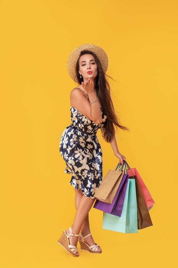 Façonnez à port de jeune femme de portrait les paniers, chapeau de paille, robe posant au-dessus du fond jaune coloré baiser images stock