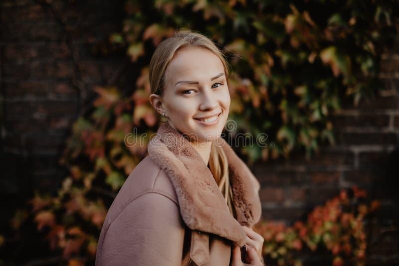 Façonnez dehors la jeune femme blonde posant sur les feuilles d'automne magiques sur le fond près du bâtiment sur la rue photos libres de droits