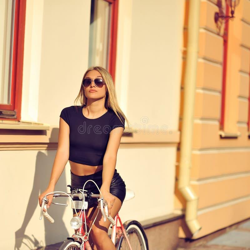 Façonnez dehors le portrait d'un beau modèle blond avec le vélo image stock