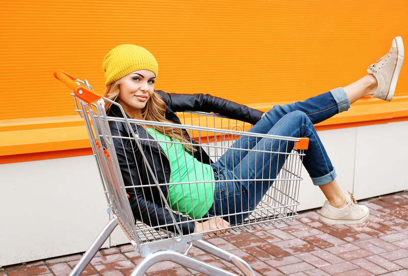 Façonnez l'équitation blonde de femme ayant l'amusement dans le chariot de chariot à achats images stock