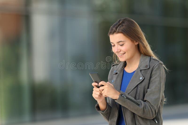 Façonnez l'ado utilisant un téléphone intelligent sur la rue photos libres de droits