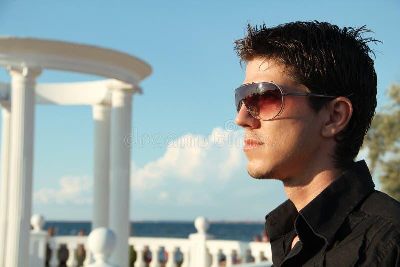 Façonnez l'homme bel dans des lunettes de soleil, dehors portrait photographie stock