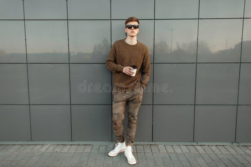 Façonnez l'homme bel de hippie avec du café dans des lunettes de soleil photos libres de droits
