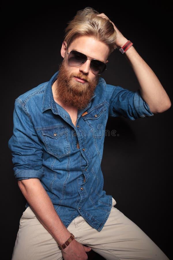 Façonnez l'homme dans la séance et la fixation bleues de chemise ses cheveux photos stock