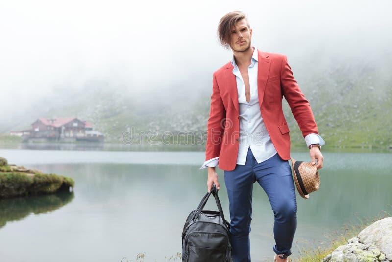 Façonnez l'homme tenant son sac de chapeau et de voyage près du lac images libres de droits