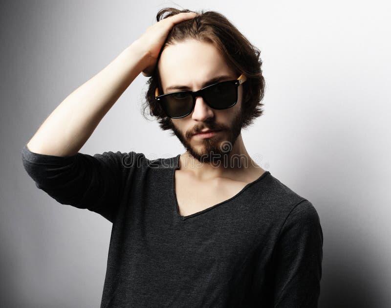 Façonnez l'homme utilisant les lunettes de soleil à la mode sur le fond blanc photographie stock