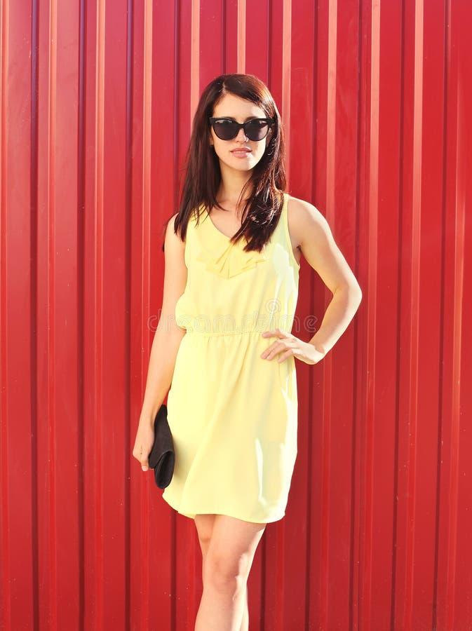 Façonnez la belle femme de brune utilisant la robe et les lunettes de soleil jaunes avec l'embrayage de sac à main dans la ville photos stock