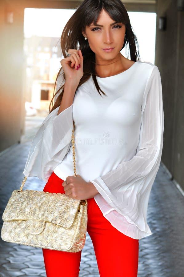 Façonnez la belle femme sensuelle de brune dans le chemisier blanc de pantalon de rouge tenant le sac d'or image stock
