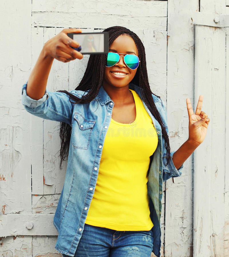 Façonnez la femme africaine assez jeune prenant la photo d'autoportrait sur un smartphone photographie stock libre de droits