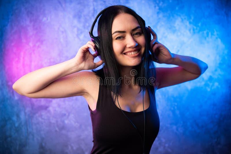 Façonnez la femme assez fraîche dans des écouteurs écoutant la musique au-dessus du rose et du fond au néon bleu Beau jeune adole photographie stock