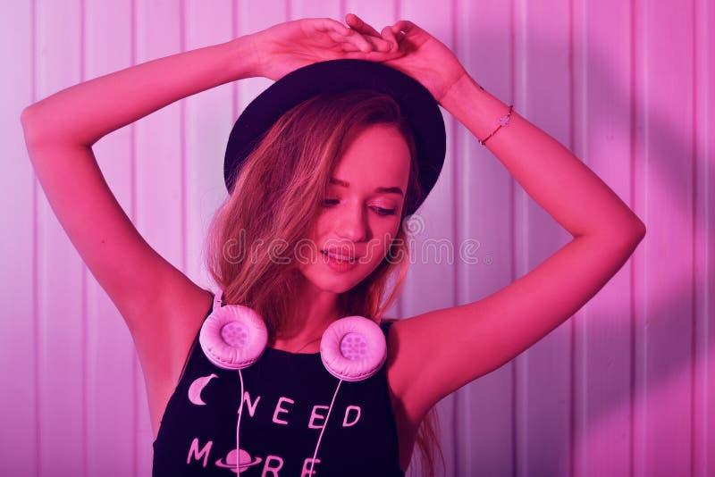 Façonnez la femme assez fraîche dans le chapeau et des écouteurs écoutant la musique au-dessus du fond au néon rose Belle jeune a images stock