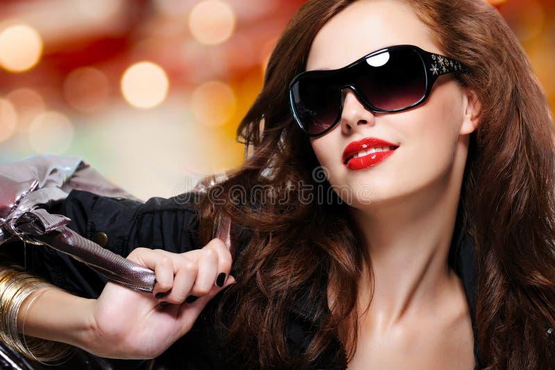 Façonnez la femme dans des lunettes de soleil à la mode noires avec le sac à main image stock