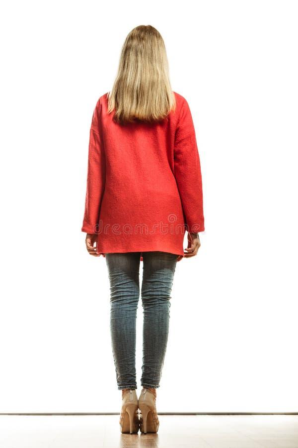 Façonnez la femme dans la vue arrière de manteau rouge vif de couleur photos stock