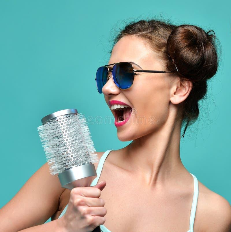 Façonnez la femme de brune chantant avec la grande brosse de cheveux dans des lunettes de soleil modernes d'aviateur images stock