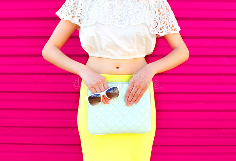 Façonnez la femme de charme avec l'embrayage et les lunettes de soleil de sac à main au-dessus du rose coloré photo stock
