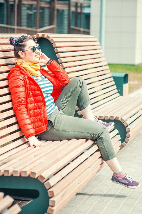 Façonnez la femme de hippie avec les cheveux colorés se reposant sur le banc photographie stock